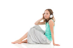 Relaxing with the music. Young girl sitting on the floor with headphones and listening to the music. Full length studio shot isolated on white Stock Image