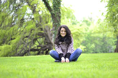 Relaxing nature - beautiful healthy woman sitting on the grass Royalty Free Stock Photography