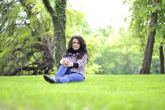 Relaxing nature - beautiful healthy woman sitting on the grass Stock Photography