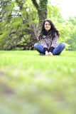 Relaxing nature - beautiful healthy woman sitting on the grass Stock Images