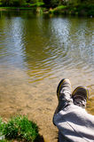 Relaxing in nature. Legs beside a river, admiring the view Stock Photos
