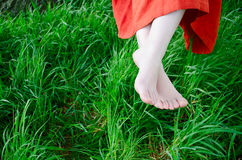 Relaxing in nature. A young womans feet amongst green grass in nature Stock Photo