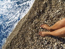 Relaxing near waters edge. View of female legs and bare feet on beach near waters edge; woman's upper body and face not in photo Stock Images