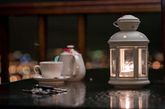Relaxing night. Candle, keys, pot and cup on the table in the relax night Royalty Free Stock Photo