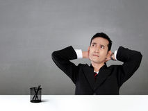 Relaxing office worker looking up with thoughtful face. Young Asian businessman sitting and relaxing in front of his desk, looking up with thoughtful facial Stock Photos