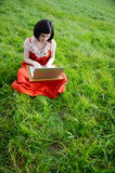 Relaxing online work in nature. A young woman sitting in a field working on a laptop Stock Images