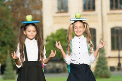 Relaxing organic food break. Calm children hold books and apples on head. School snack. Organic food. Healthy eating