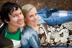 Relaxing Outdoor Couple. A couple smiling at the camera relaxing outdoors royalty free stock photo