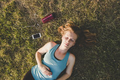 Relaxing outdoor. Young woman relaxing in the park after running.  Royalty Free Stock Photo