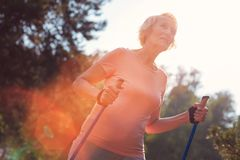 Portrait of old woman walking with a help of crutches. Relaxing outdoors. Portrait of smiling old woman spending time in fresh air while walking with a help of Royalty Free Stock Photo