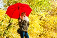 Woman walking in park with umbrella. Relaxing outside concept. Woman walking in park with red umbrella, autumn bright weather Royalty Free Stock Images