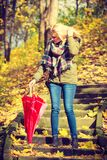 Woman walking in park with umbrella. Relaxing outside concept. Woman walking in park with red umbrella, autumn bright weather Royalty Free Stock Photos