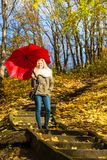 Woman walking in park with umbrella. Relaxing outside concept. Woman walking in park with red umbrella, autumn bright weather Stock Image
