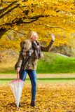 Woman walking in park with umbrella. Relaxing outside concept. Woman walking in park with umbrella, autumn bright weather Stock Photos