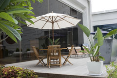Relaxing outside on a Patio. Luxury apartments - This is a scenic patio in front of glass fronted building. The scene is relaxed with plants, bbq grill, table stock photography