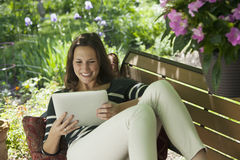 Relaxing outside reading a digital tablet Royalty Free Stock Images