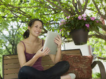 Relaxing outside reading a digital tablet Royalty Free Stock Photo
