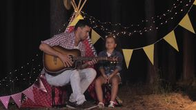 Relaxing with parent, beautiful curly girl has fun talking with her father and playing guitar during forest party on stock video
