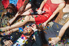 Relaxing at party. Realxed guys lying by legs of girls at party Royalty Free Stock Image