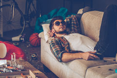 Relaxing after party. Young handsome man in sunglasses lying down on sofa with joystick in his hand in messy room after party stock photography