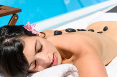 Relaxing with pebbles in spa. Woman relaxing and sunbathing in spa club at poolside in summer Stock Images