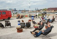 Relaxing people at lounge area of riverside street market Reffen, urban space for start-ups and leisure. COPENHAGEN, DENMARK - SEPT 7: Relaxing people at lounge royalty free stock photos