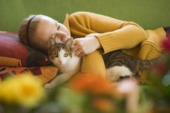 Relaxing with pet. Cat and girl on a green sofa Stock Photos