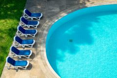 Relaxing plastic chairs by the swimming pool side. Stock Photography