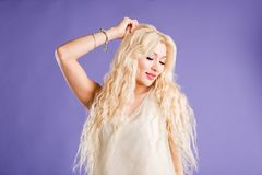 Smiling beautiful blonde woman on violet background stock image