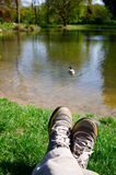 Relaxing beside a pond. Legs beside a river, admiring the view Stock Photo