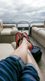 Relaxing on a Pontoon boat on a cloudy summer day. Relaxing in flip flop on a boat Stock Photos