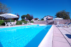 Relaxing by pool. Relaxing by the pool on a sunny day with a blue sky at a villa in France Stock Photography
