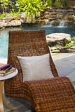 Relaxing pool oasis with waterfall and chaise Royalty Free Stock Photos