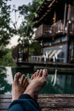 Relaxing by the pool. A shot of a person crossed legs relaxing by the pool Royalty Free Stock Photos