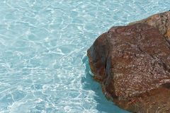 Relaxing Poolside background. Relaxing Poolside image of Turquoise clear crystal water at a pool side with a large brown wet rock ideal set for background copy stock photos