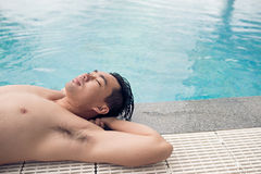 Relaxing at poolside. Handsome Asian man relaxing at the poolside Royalty Free Stock Photography