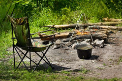 Relaxing and preparing food on campfire in camping Stock Photography