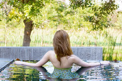 Relaxing pretty swimsuit fashion young sexy asian woman with luxury pool resort in nature Stock Image