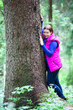Relaxing pretty woman standing cheek to tree Royalty Free Stock Image