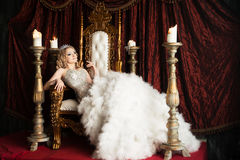 Relaxing queen on the throne. Joy, pleasure. Royal Royalty Free Stock Photography