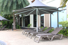 Relaxing rattan chairs with a big umbrella beside the swimming pool Royalty Free Stock Photo