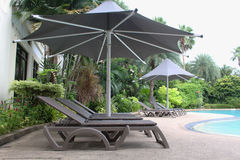 Relaxing rattan chairs with a big umbrella beside the swimming pool Stock Image