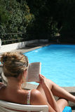 Relaxing read. Reading by the pool Stock Images