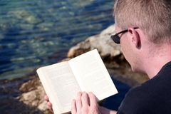 Relaxing while reading. Man an vacation, relaxing while reading at the seaside Royalty Free Stock Photo
