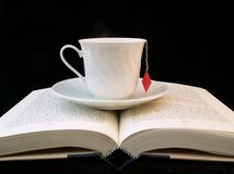 Relaxing reading. Teacup on an open book royalty free stock photography