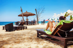 Relaxing and reading on the beach Royalty Free Stock Photos