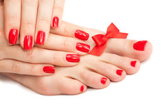 Red manicure and pedicure with a bow Royalty Free Stock Photography