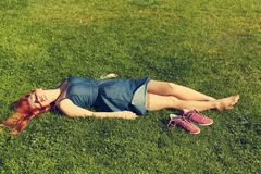 Relaxing redhead girl lying on grass. woman relaxation outdoor. Relaxing redhead girl lying on the grass. woman relaxation outdoor royalty free stock photos