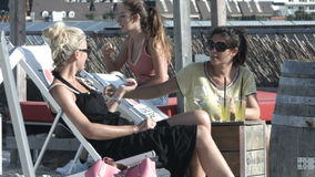A relaxing and refreshing time with friends. Two young women relaxing in lounge chairs having a conversation. Another girl sits behind them stock footage