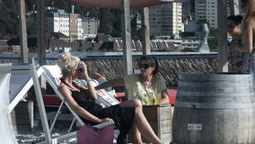A relaxing and refreshing time with friends. Two young women relaxing in lounge chairs having a conversation. People walking by on Sky Beach Stuttgart stock video footage